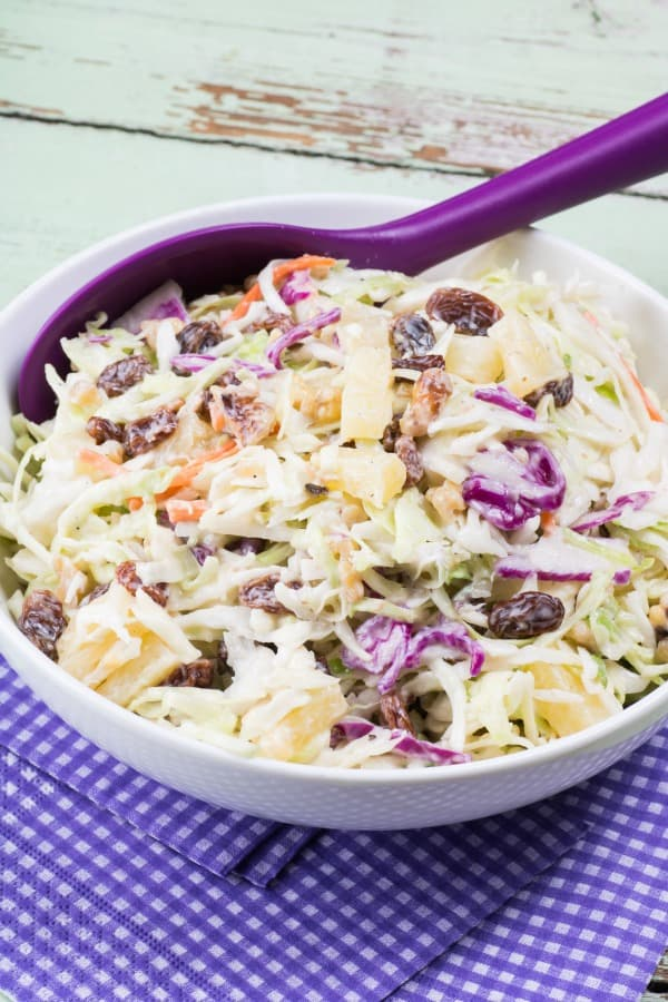 Pineapple Walnut Raisin Coleslaw in a bowl with a serving spoon
