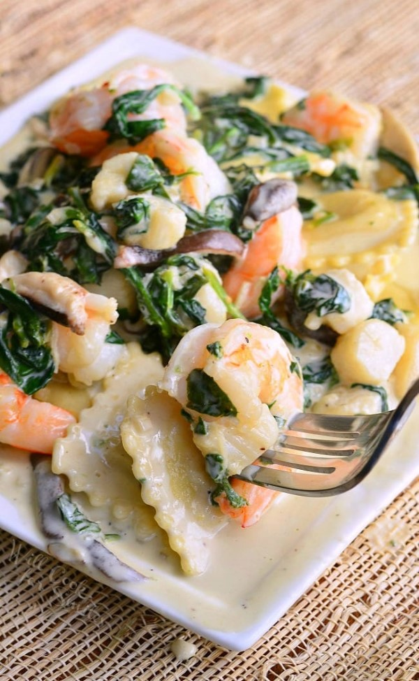 Ravioli with Seafood, Spinach and Mushrooms in a Garlic Cream Sauce on a white plate