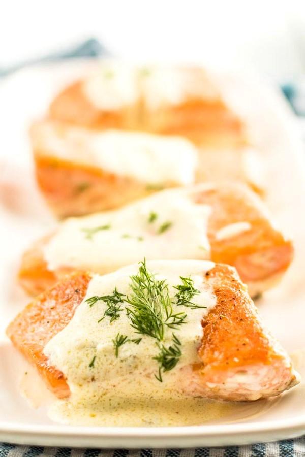 Salmon with Creamy Lemon Dill Sauce (Keto) on a white platter