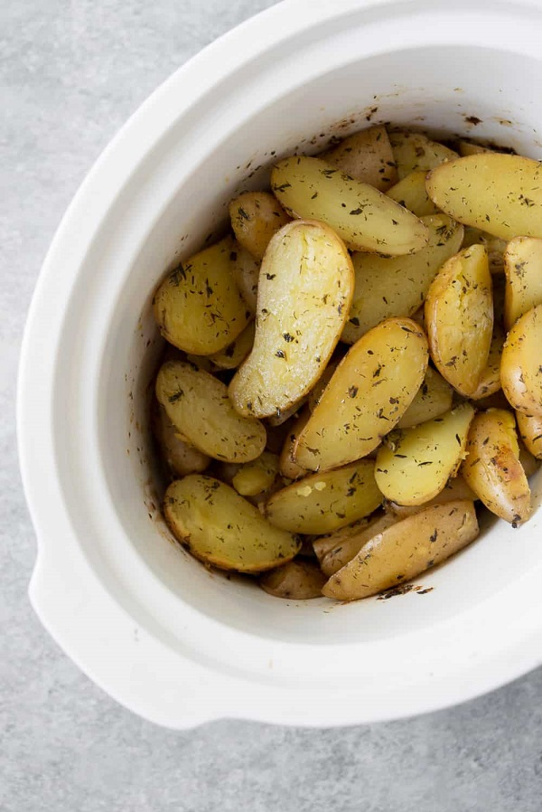 Slow-cooker garlic herb potatoes in a white serving bowl