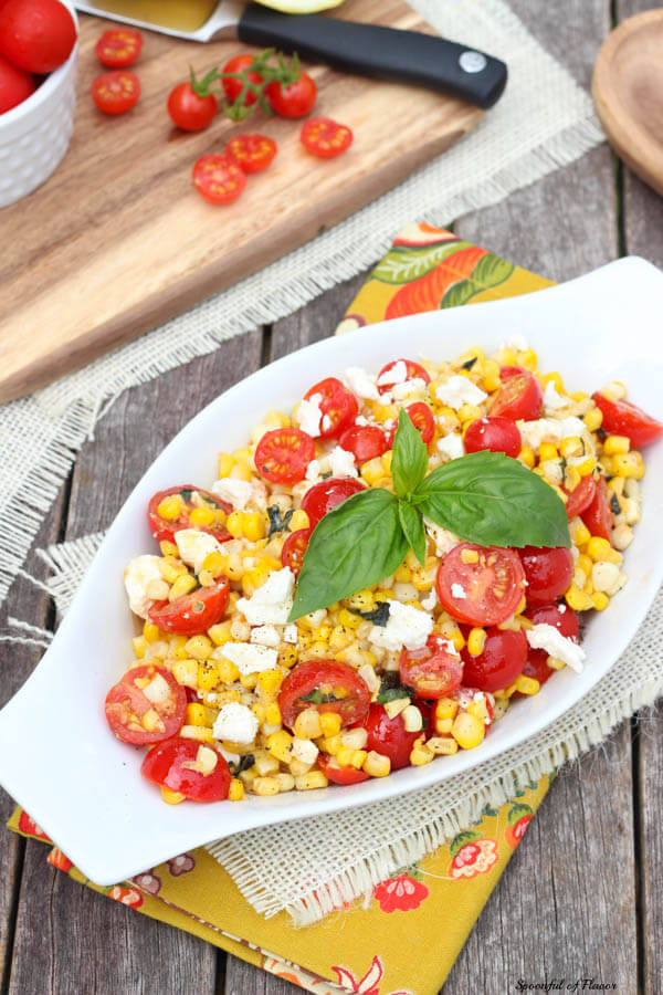Sauteed corn with tomatoes feta and basil in a white serving dish