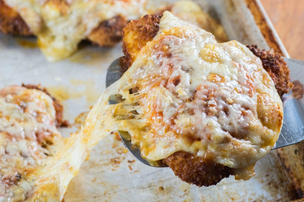 Turkey Cutlets Parmesan on a spatula with ooey gooey cheese