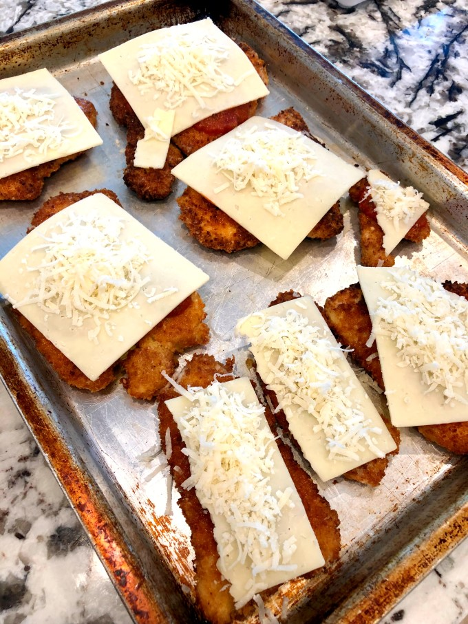 Turkey cutlets on a baking sheet topped with cheese ready for the oven.
