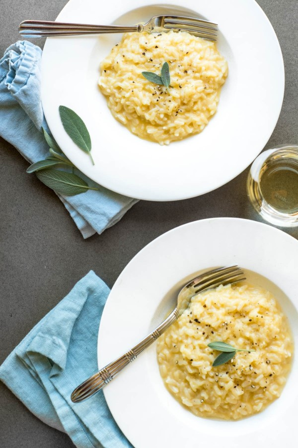 Instant Pot Cheddar Risotto with Fresh Sage in white bowls with forks