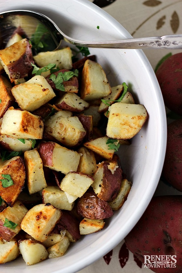 Garlic roasted potatoes in a white serving dish