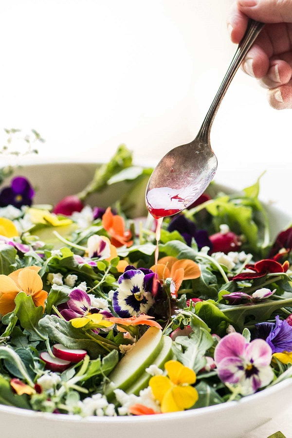 Winter Pansy Salad with a spoon drizzling dressing in a white serving bowl