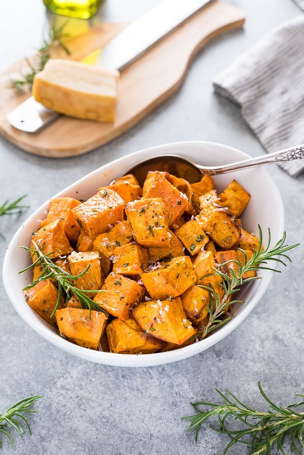 Rosemary Parmesan sweet potatoes in a white serving dish