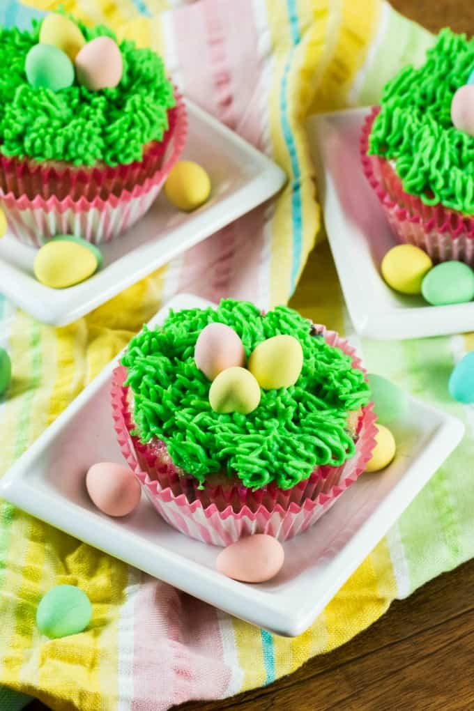 Easter Cupcakes on little white dishes with Easter eggs.