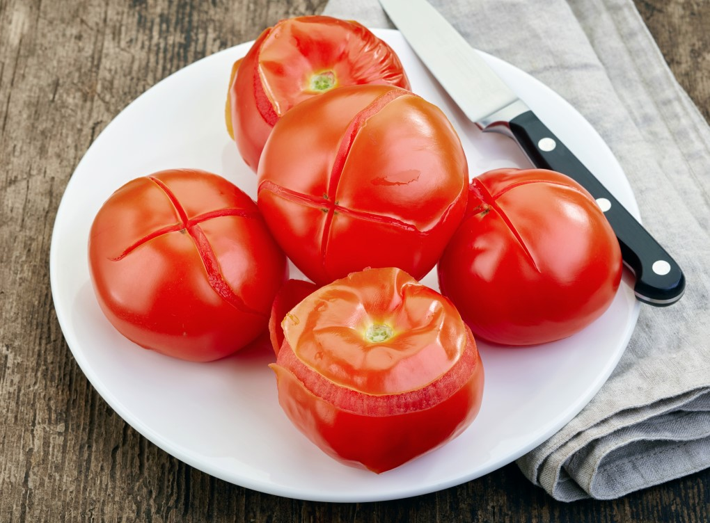 Tomatoes on a white plate with the skins peeling after being boiled.