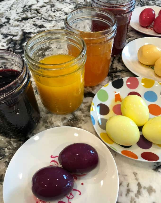 Jars of dye and dyed eggs on plates