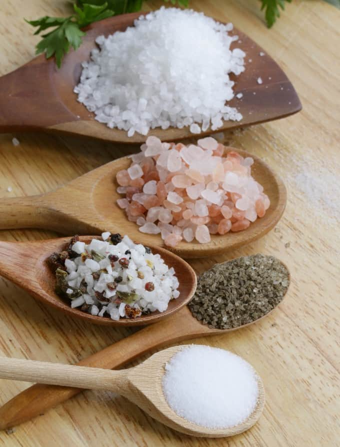 Different types of salts in wooden spoons on a wood board.