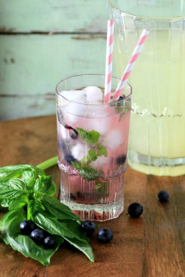 Blueberry Basil Lemonade in a glass with pink and white straws