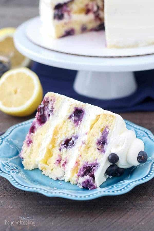 Blueberry Lemon Mascarpone Cake sliced on a light blue plate with the cake in the background