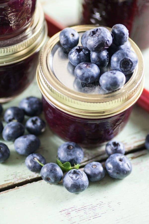 Blueberry Rhubarb Jam in a jar with blueberries on top