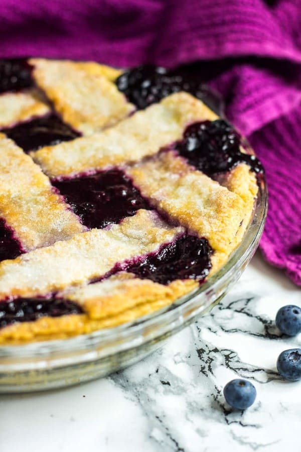 Homemade Blueberry Pie on a granite counter top with a purple napkin