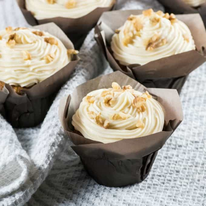 Carrot Cake Cupcakes on a grey and white tea towel.