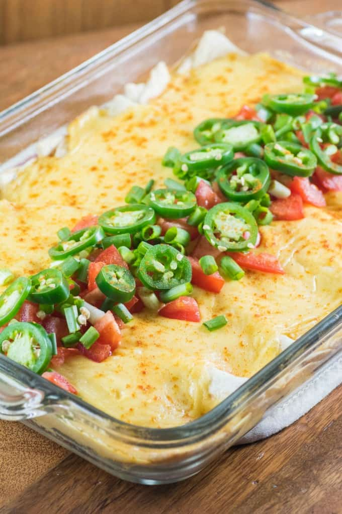 Cheesy Ground Turkey Enchiladas in a casserole dish with jalapeno tomato topping