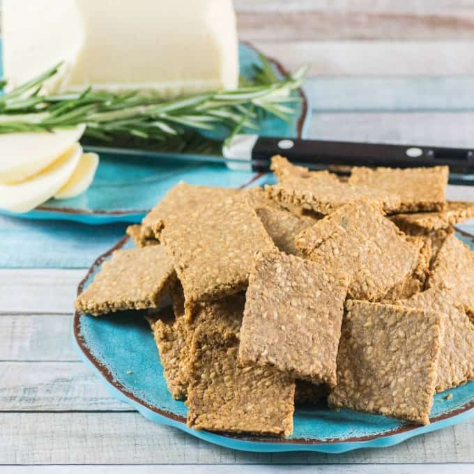 Gluten Free Crackers Recipe on a blue plate with sliced white cheese in the background.