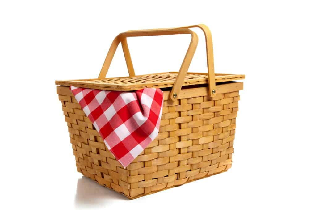 A traditional picnic basket with a checkered table cloth hanging out