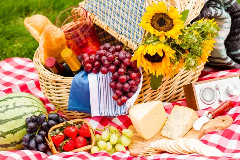 Picnic basket with food, fruit, wine, cheese, sunflowers overflowing onto a checkered table cloth
