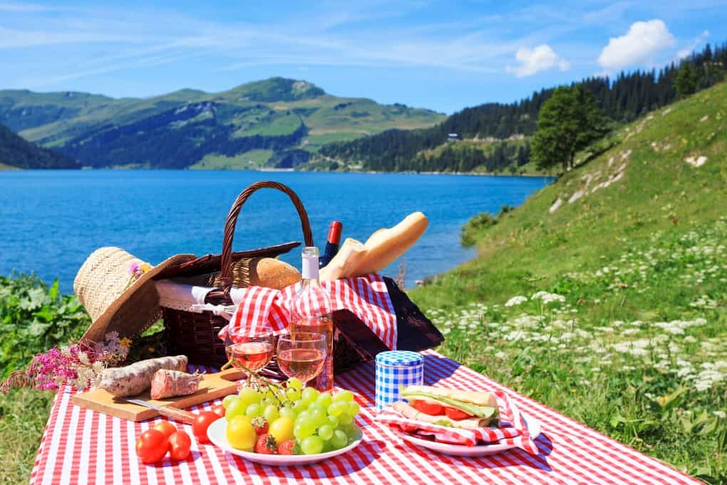 Picnic set up on a traditional checkered cloth over looking a lake and mountains