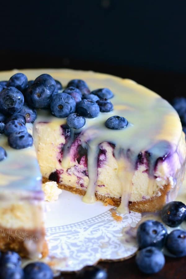 White Chocolate Blueberry Cheesecake on a white platter with fresh blueberries