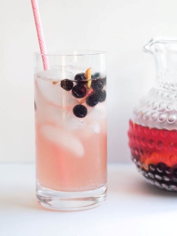 Blueberry Kombucha Sangria in a tall glass with a straw