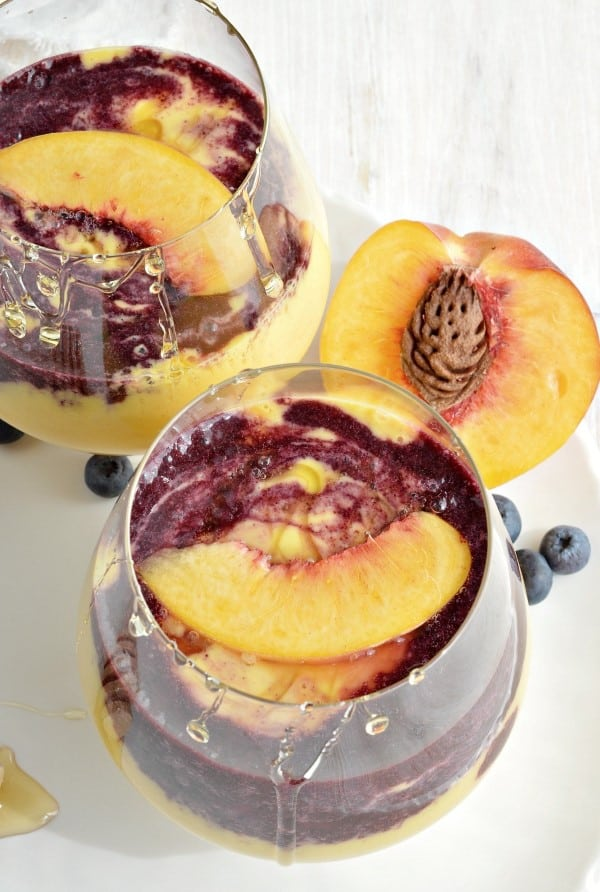 Peach Smoothies with Wild Blueberry Swirl in glasses on a white plate