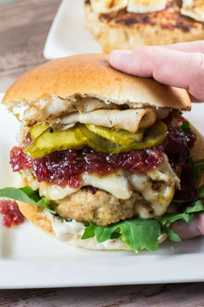 A hand reaching in to grab a Giant Juicy Turkey Burger