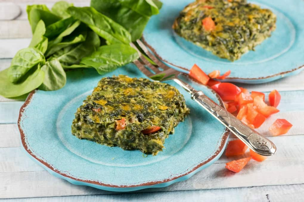Spinach squares on blue plates with a fork, red pepper and spinach