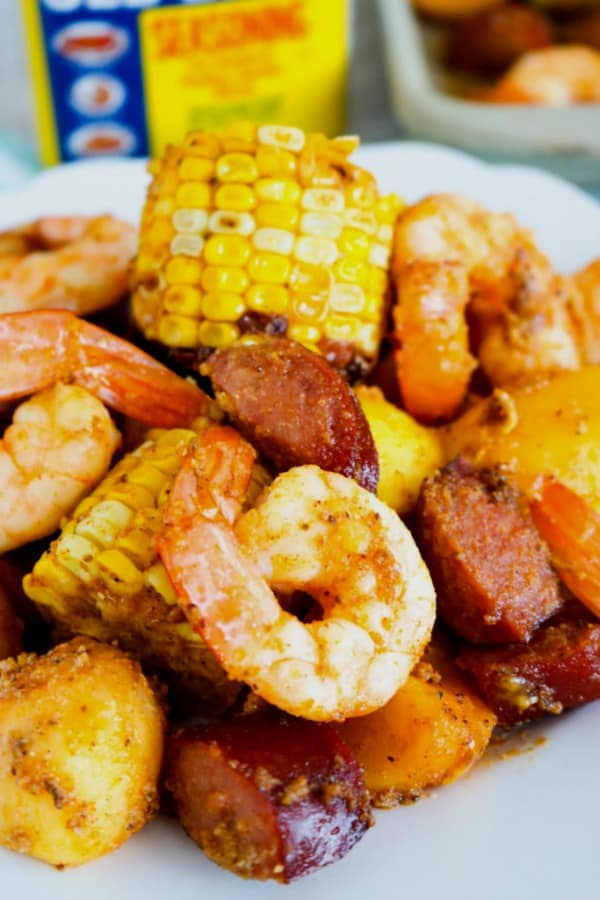 Corn, shrimp, sausage and shrimp on a white plate with Old Bay Seasoning in the background