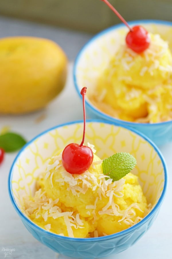 Mango pineapple sorbet in a blue bowl with coconut a cherry and a mint leaf on top
