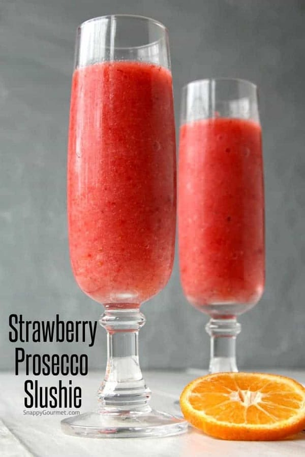 Strawberry prosecco slushie in a champagne flute with an orange slice
