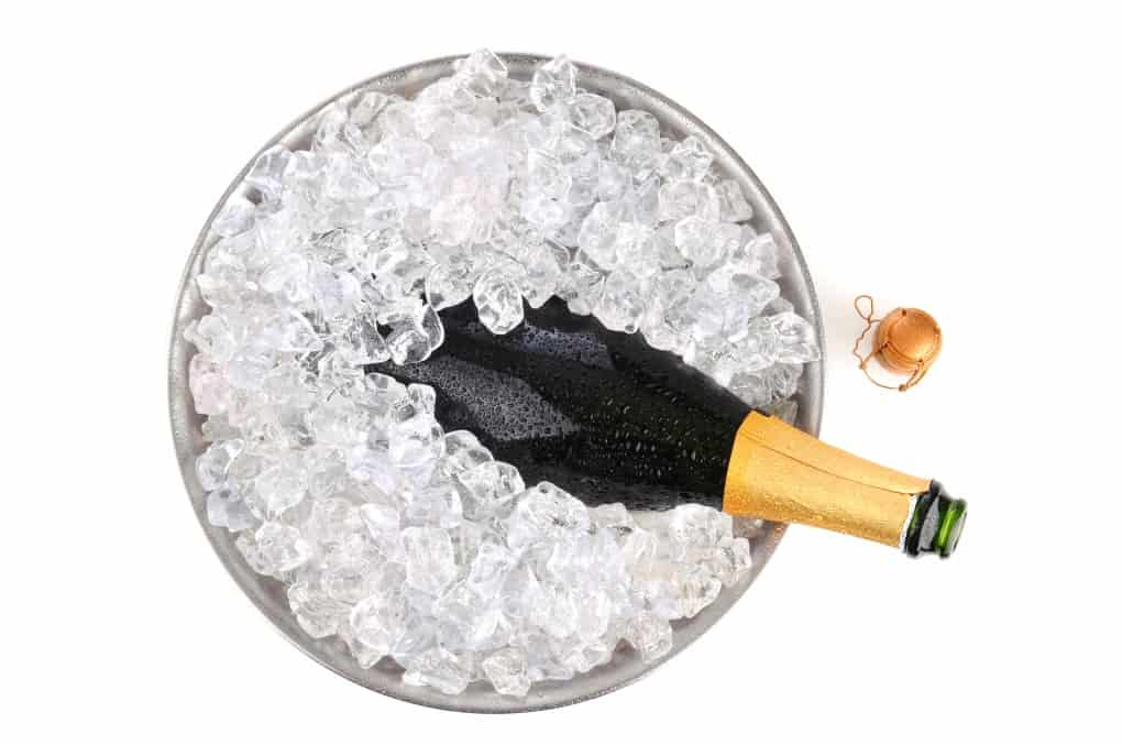Bottle of Champagne in a cooler of ice with the wire cage on the table.