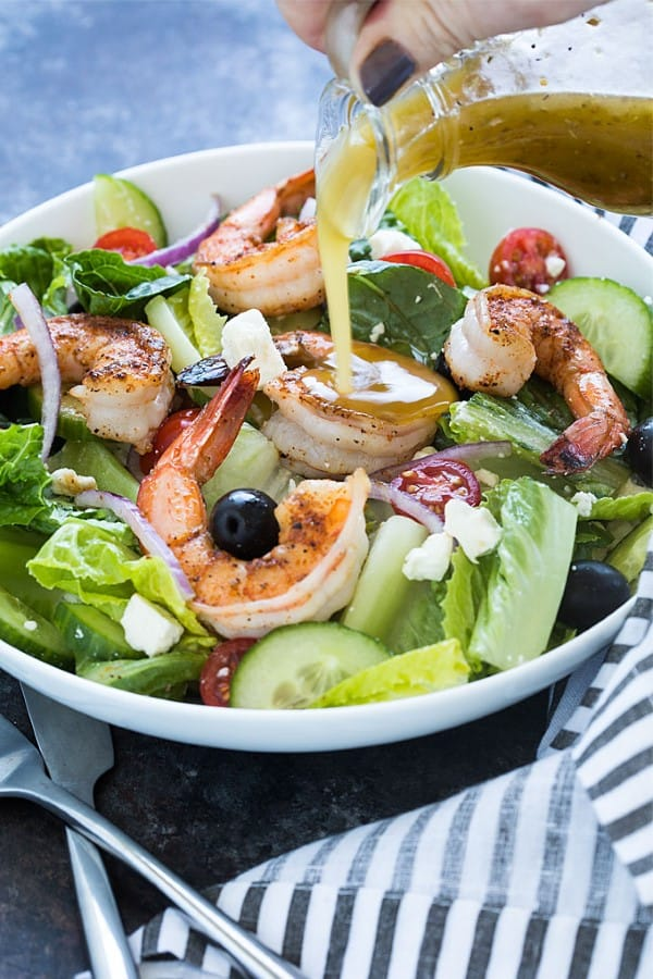 GREEK SALAD WITH BLACKENED SHRIMP in a bowl with dressing being poured on.