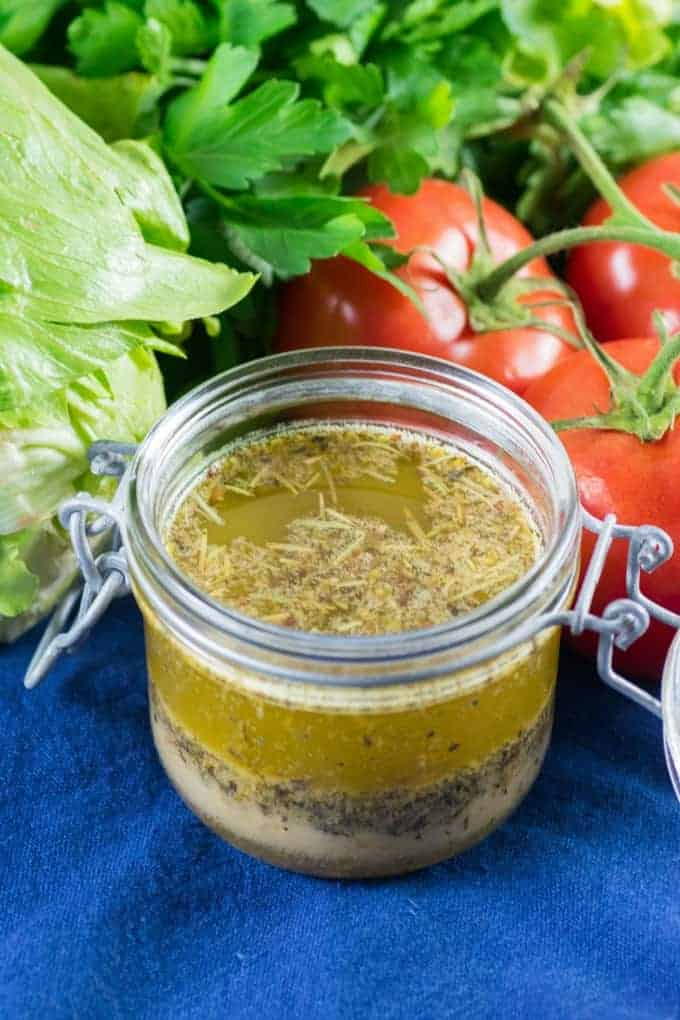 Homemade Italian Dressing in a small jar with tomatoes, lettuce and herbs