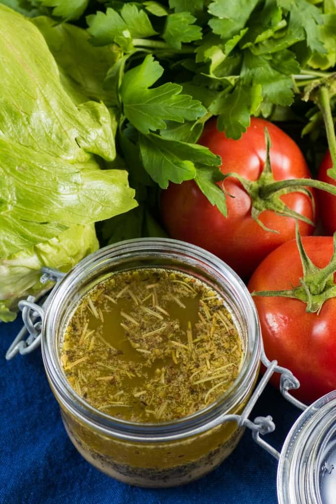 Overhead view of homemade Italian dressing in a jar with fresh produce