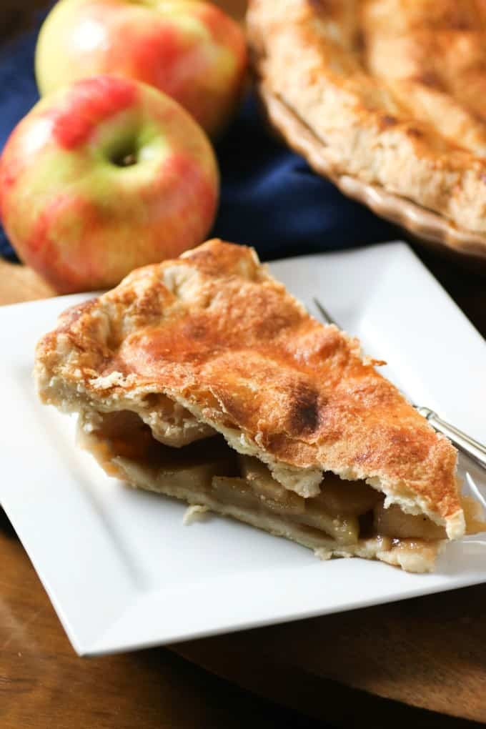 Slice of apple pie on a white plate with apples in the background