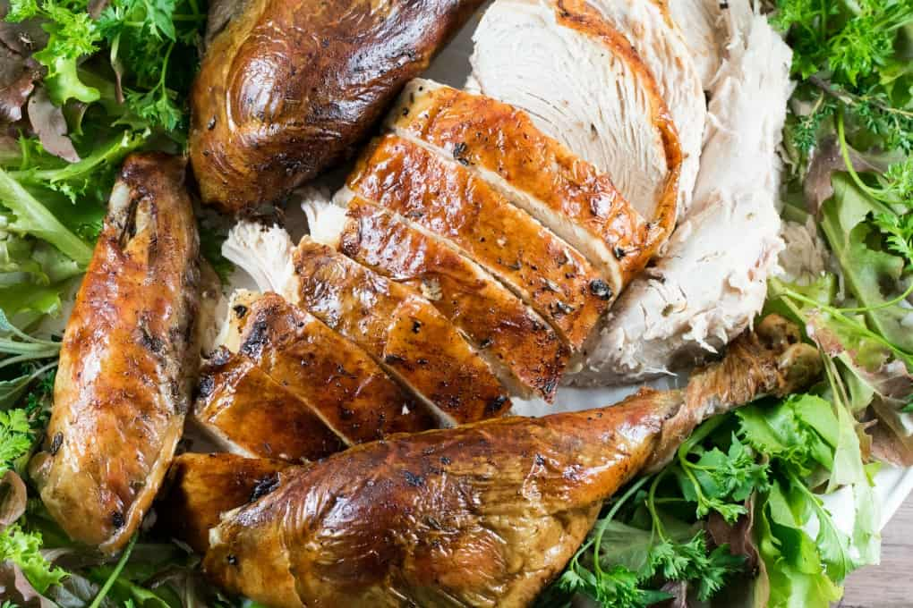 Sliced up roast turkey on a platter with greenery