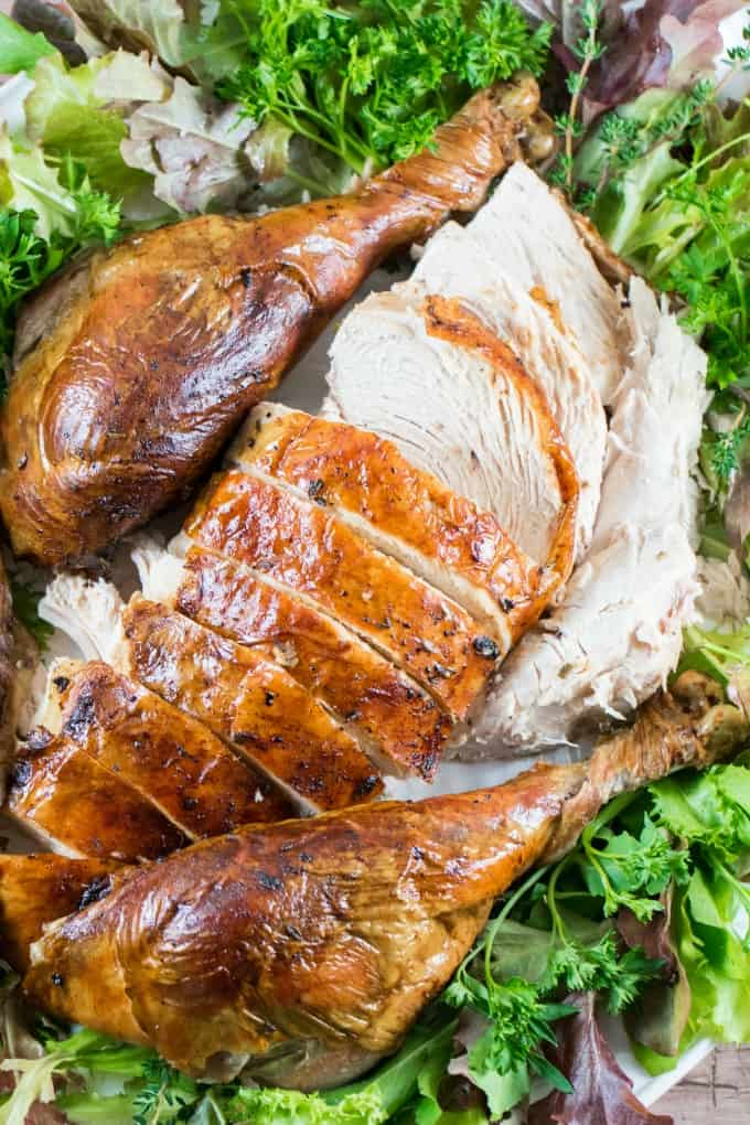Cheesecloth Herb Butter Turkey Recipe on a platter cut up with greenery