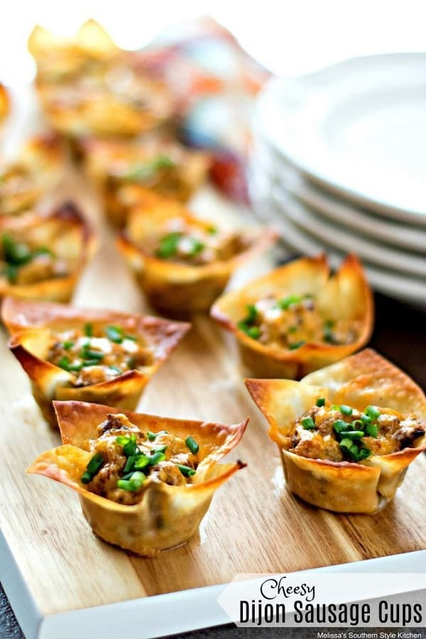 Cheesy Dijon Sausage Cups in a wooden board with white plates at the side