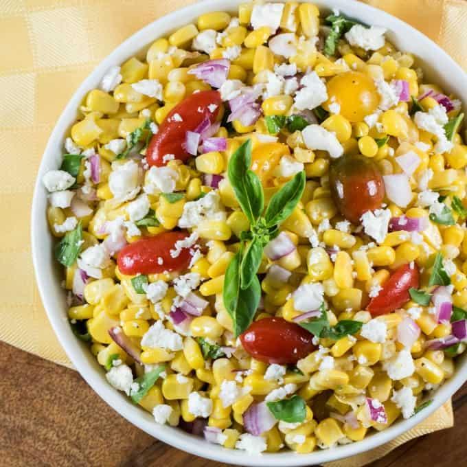 Overhead view of Cojita Corn Salad Recipe in a white bowl with a yellow napkin underneath.
