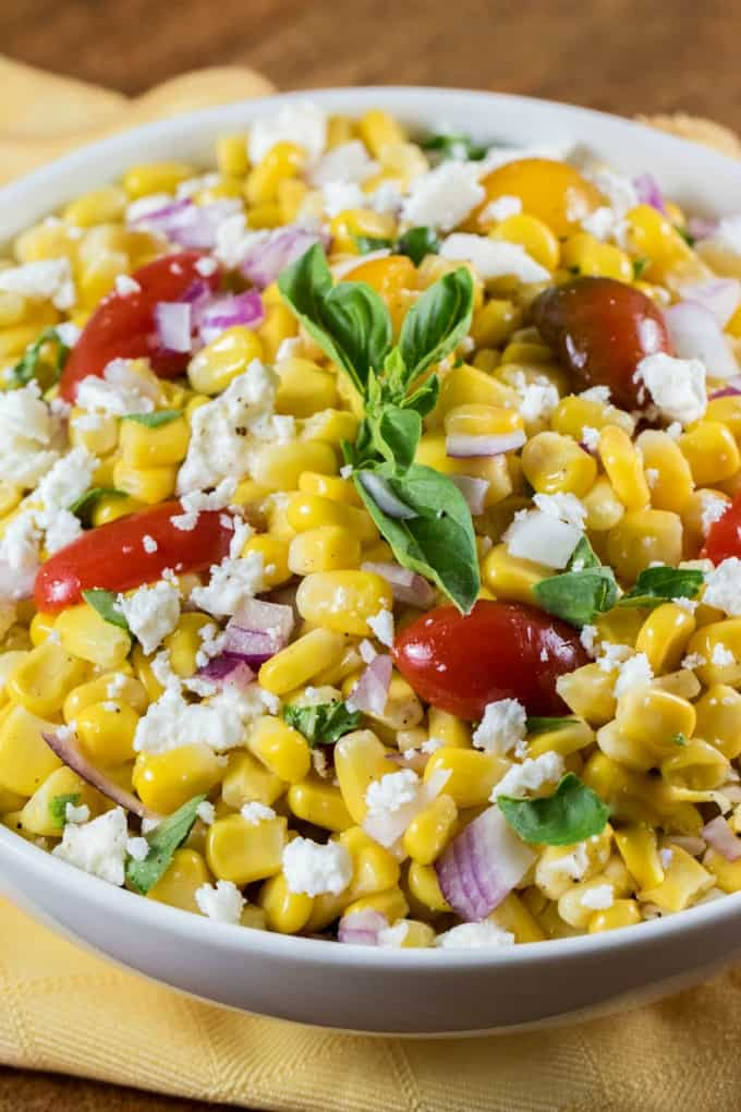 Close up of Cotija Corn Salad Recipe in a white bowl over a yellow napkin