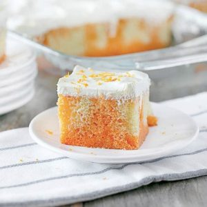 Square slice of orange creamsicle poke cake on a plate