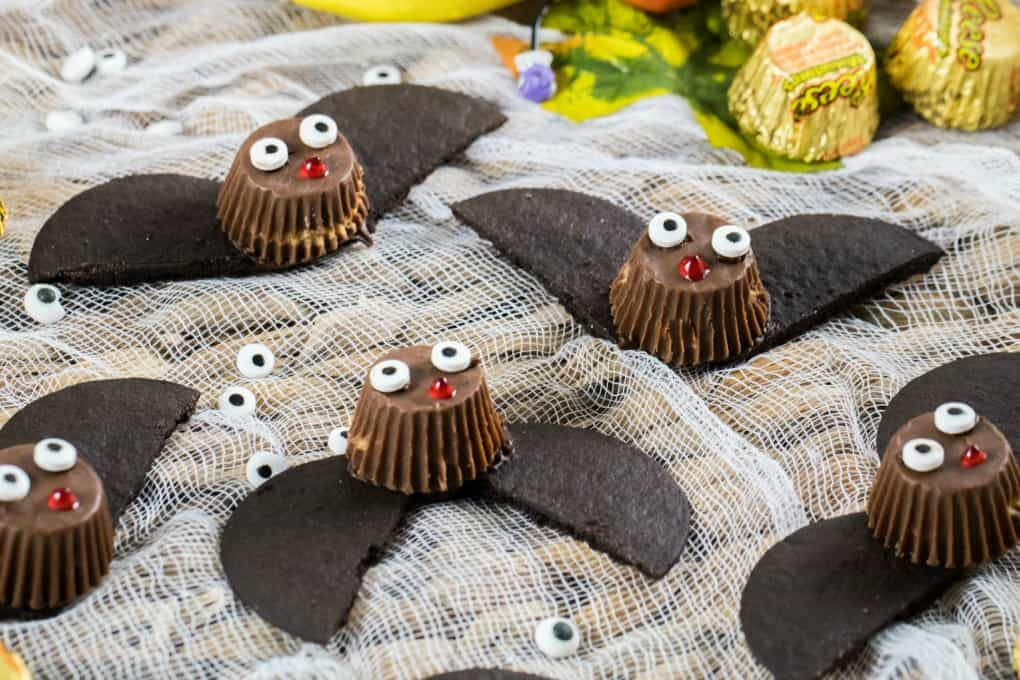 Easy Bat Peanut Butter Cups on a tray with cheesecloth and fall decorations of leaves, Reese's and eyeballs.