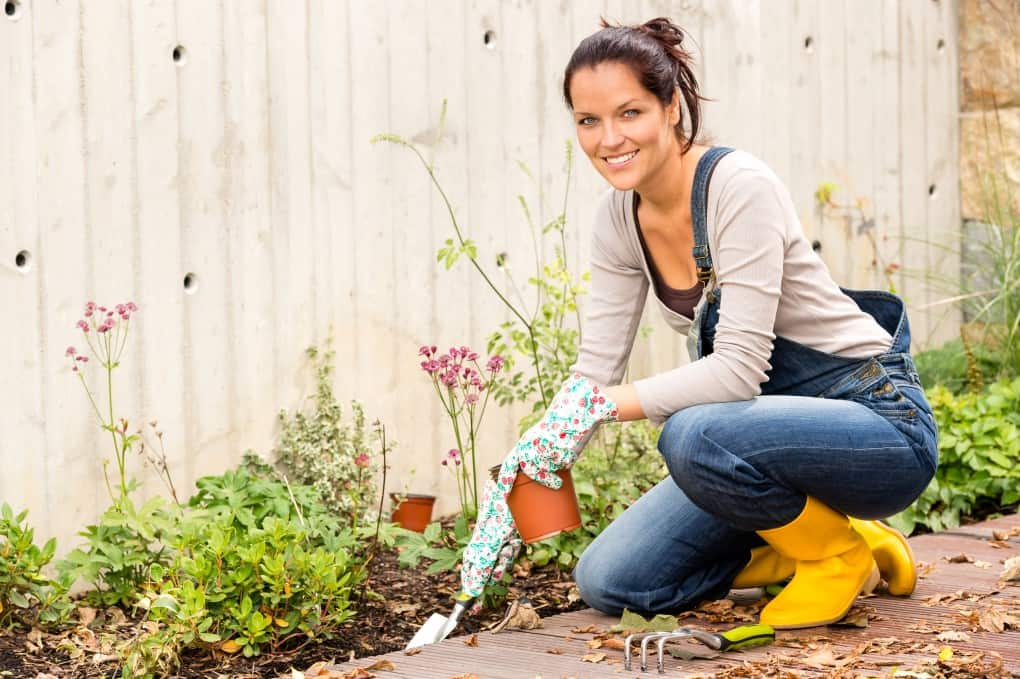 Pretty woman cleaning up the garden in fall for Fall Garden Tips to Get You Ready for Winter