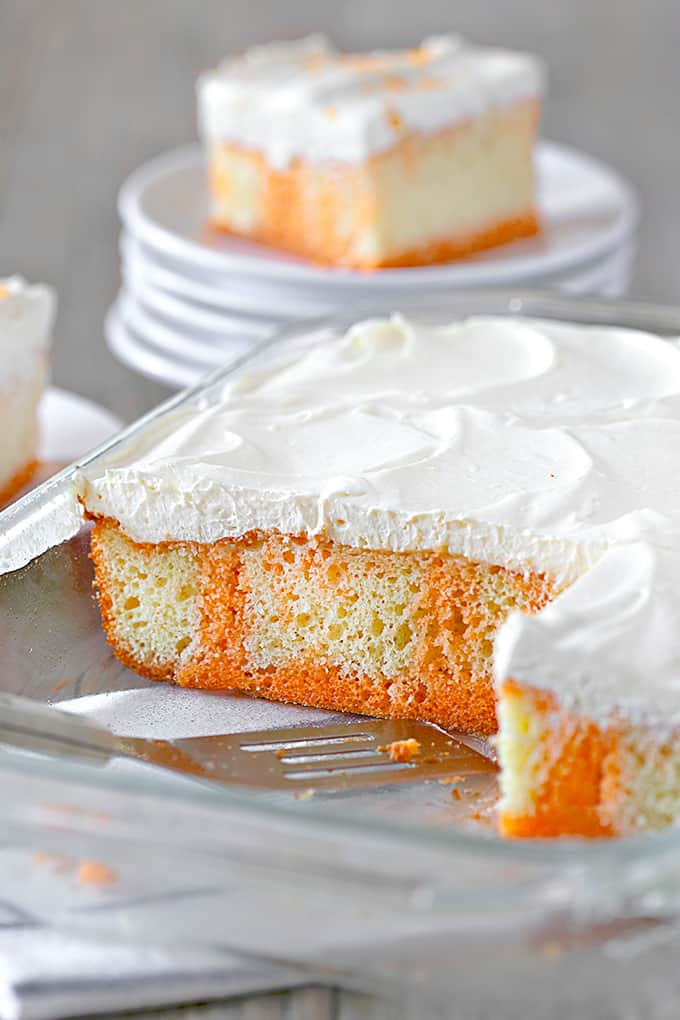 Orange Creamsicle Poke Cake in a cake pan with a slice on plates in the background