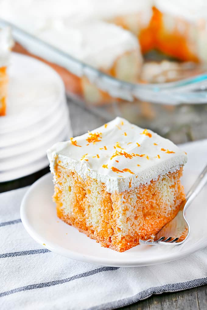 Close up of a slice of Orange Creamsicle Poke Cake on a white plate with a fork