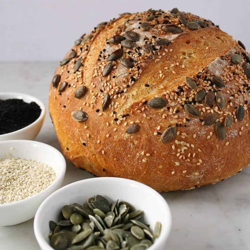 Pumpkin No Knead Bread - Bread boule topped with various seeds, surrounded by small bowls filled with the same seed.