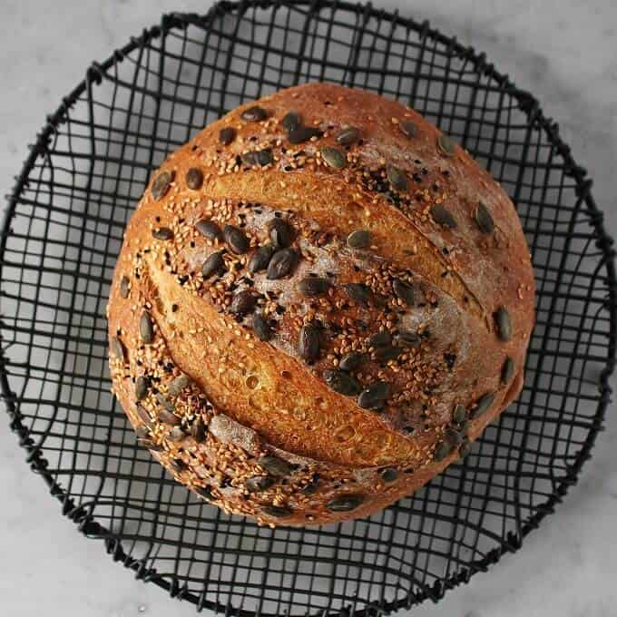 Pumpkin No Knead Bread - Bread Boule topped with assorted seeds on a black cooking rack.